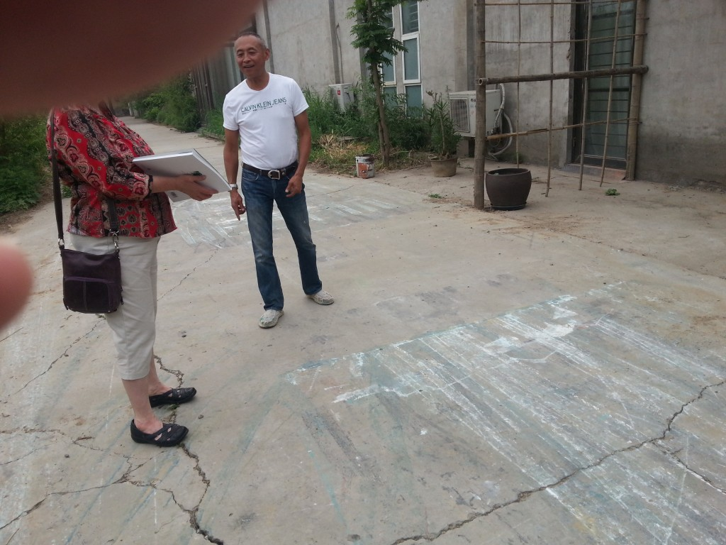 Artist Zhang Wei and Debbie inspecting how he paints using his motorcycle in his driveway.