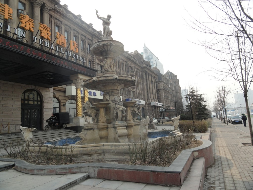 shot of fountain and front of Tehall Hotel showing neon Chinese character signs
